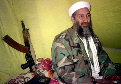 Osama bin Laden dressed in camouflage, in secret hideout with AK47 propped against a wall